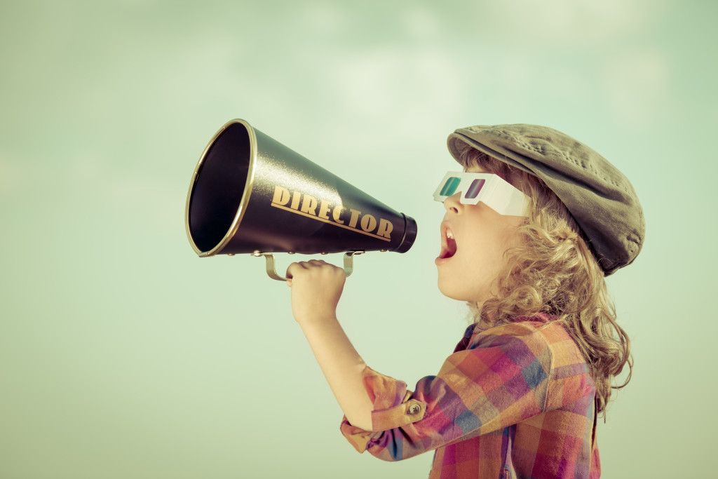 Child talking into megaphone acting
