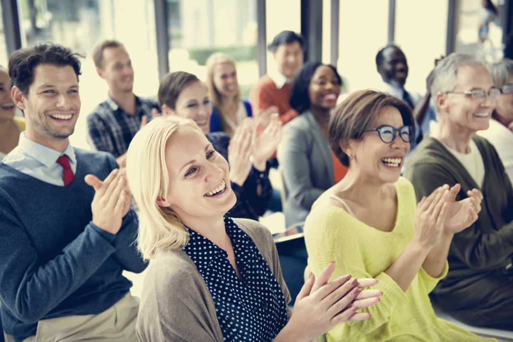 A group of people smiling and clapping as they listen and relate to a public speaker